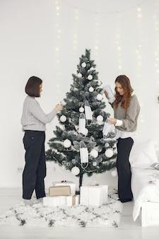 Coronavirus en kerstconcept. vrouwen thuis. dame in een grijze trui.