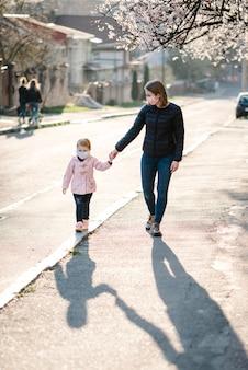Coronavirus en luchtverontreiniging concept. klein meisje en moeder dragen maskers lopen op straat. symptomen van pandemisch virus.