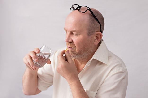 Coronavirus gevarenconcept voor ouderen. een man neemt medicijnen.