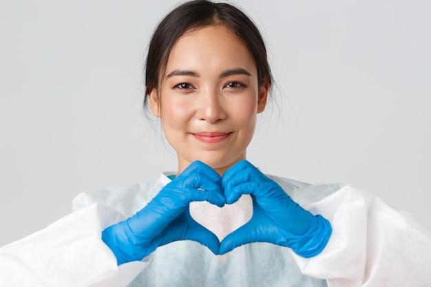 , coronavirus, gezondheidswerkers concept. close-up van uitgeputte gelukkige aziatische vrouwelijke arts start persoonlijke beschermingsmiddelen, heeft huidafdrukken van gasmasker, toont hartgebaar