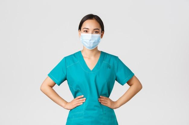 , coronavirus, gezondheidswerkers concept. vrolijk lachende aziatische vrouwelijke arts, arts in scrubs en medisch masker, op zoek naar optimistisch, werken met patiënten in het ziekenhuis