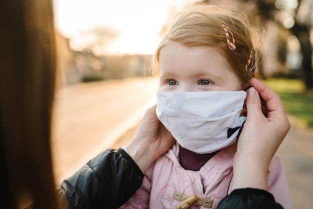 Coronavirus het eindconcept. geen covid-19 meer. klein meisje, moeder dragen maskers lopen op straat. moeder verwijdert masker gelukkig kind. gezin met kind buitenshuis. succes vieren. pandemie is voorbij, is afgelopen.