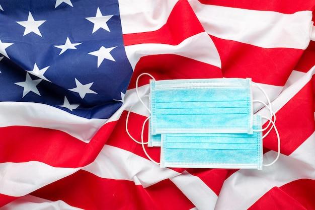 Coronavirus in de verenigde staten. beschermend chirurgisch gezichtsmasker op amerikaanse nationale vlag