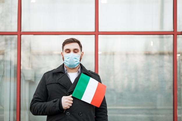 Coronavirus in italië verspreidt zich. man in medisch masker, beschermend masker met italiaanse vlag. virusepidemie, chinese coronavirusm-uitbraak influenza. luchtverontreiniging, nieuw coronavirus in europa eu. Premium Foto