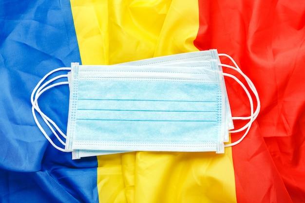 Coronavirus in roemenië. beschermend chirurgisch gezichtsmasker op roemeense nationale vlag. roemenië quarantaine, bescherming coronavirus symbool van arts, verpleegkundige, medisch werker. geneeskunde gezondheidszorg. covid-19