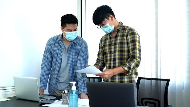 Coronavirus kantoormedewerkers met masker voor corona-viruspandemie in de wereld die op kantoor werken na afsluiting, maar de zaken moeten continu zijn.