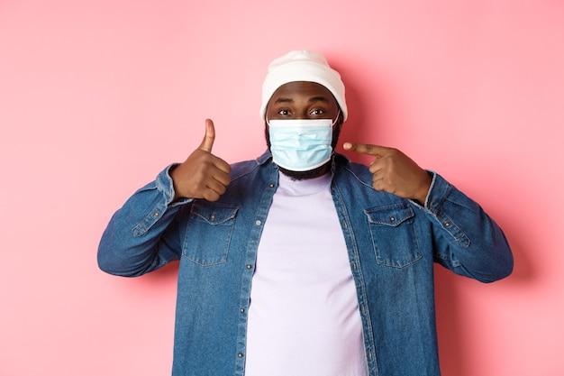 Coronavirus, levensstijl en wereldwijd pandemisch concept. jonge afro-amerikaanse man die op gezichtsmasker wijst en duimen laat zien, beschermt zichzelf tegen covid, roze achtergrond.