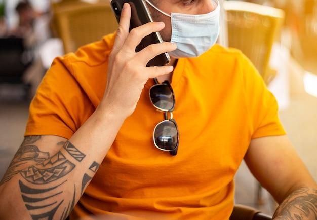 Coronavirus. man met bier, het dragen van een beschermend masker. social distancing. drink beveiliging.