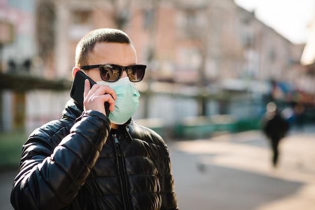 Coronavirus. mens die medisch beschermend masker draagt en op cel mobiele telefoon spreekt, die op straat loopt. voorkom covid-19, griep. je slecht voelen in de stad. persoon heeft hulp nodig. virus, pandemie, paniek concept.