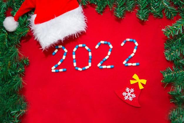 Coronavirus, ncov-19 en het nieuwe jaar. vakantie in zelfisolatie, ziekenhuis. kerstversiering en medische hulpmiddelen spuit en kerstmuts. ruimte kopiëren op een rode achtergrond