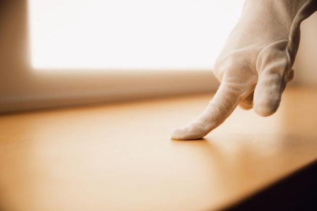 Coronavirus. nieuw coronavirus 2019-ncov, covid-29, handen van een vrouw in beschermende handschoenen die het houten oppervlak controleren op reiniging. veiligheid, bescherming, preventie, schoonmaak huis concept.
