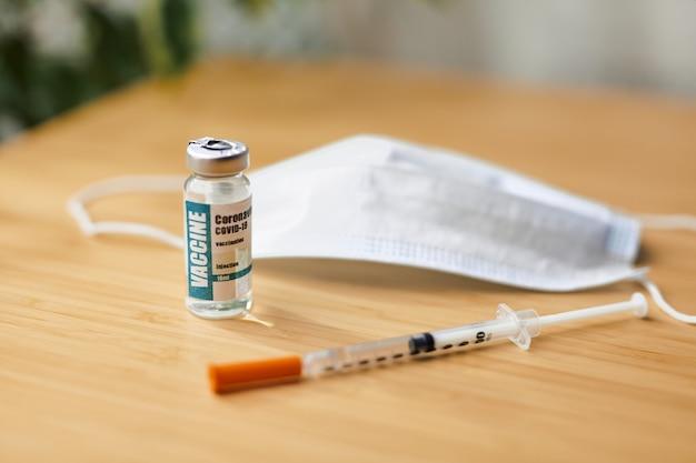 Coronavirus of covid-19, 2019 - ncov-vaccin in een fles met spuit en beschermende handschoenen en gezichtsmaak op de tafel voorbereid voor vaccinatie. covid19 concept voor onderzoek en ontwikkeling van vaccins.