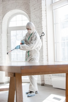 Coronavirus pandemic. een ontsmettingsmiddel in een beschermend pak en masker spuit ontsmettingsmiddelen in de kamer.