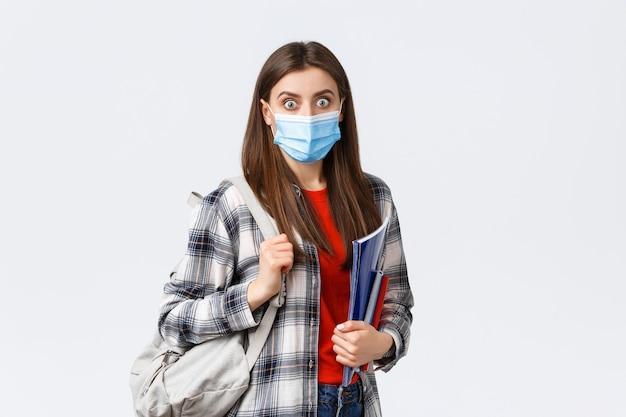 Coronavirus pandemie, covid-19 onderwijs en terug naar school concept. geschokt en verrast meisje met medisch masker, student hijgend over groot nieuws op de campus, houdt notitieboekjes en rugzak vast
