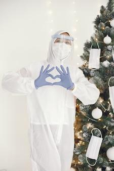 Coronavirus pandemie covid-2019. beschermend pak, bril, handschoenen, masker. kerstboom is versierd met medisch masker.