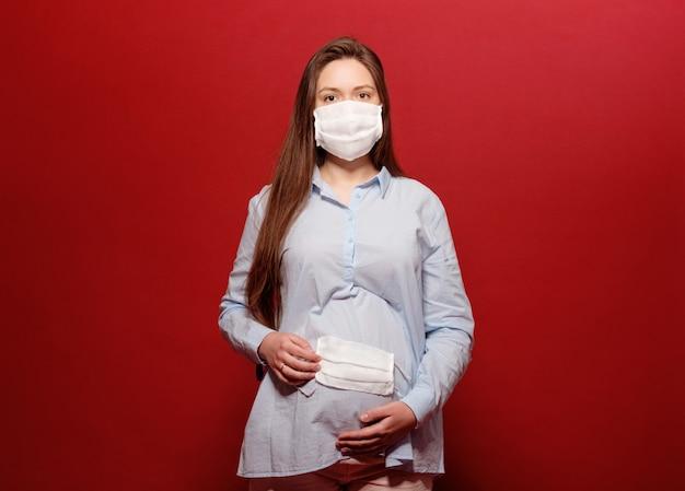 Coronavirus pandemie, jonge zwangere vrouw op rode achtergrond in beschermend medisch masker houdt op maag