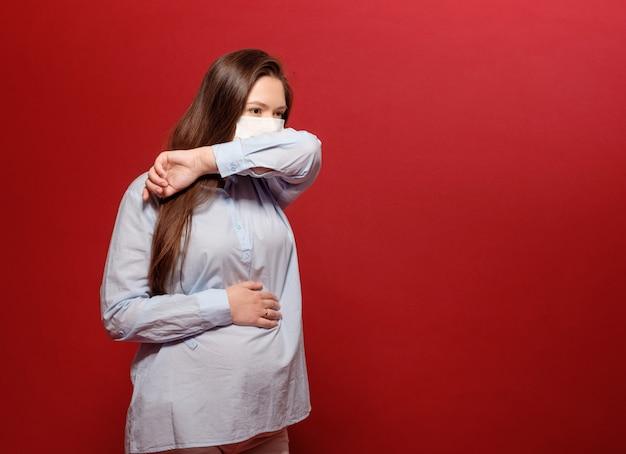 Coronavirus pandemie, jonge zwangere vrouw op rood in beschermend medisch masker houdt op maag en niest