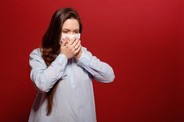 Coronavirus pandemie, niest portret van jonge vrouw op rood in beschermend medisch masker, niest