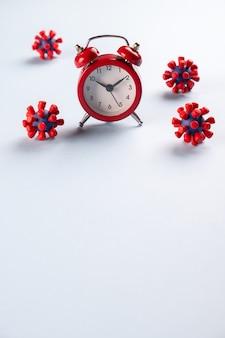 Coronavirus pandemie. tijd om thuis te blijven rode wekker en modellen van het covid-19 virus. stop het coronavirus. epidemie, sociaal isolement, coronavirus covid-19-concept.