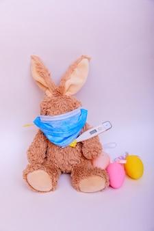Coronavirus pasen. konijn met eieren in een medische masker op een witte achtergrond. pasen in quarantaineconcept.