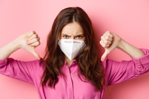 Coronavirus, preventieve maatregelen en gezondheidsconcept. close-up portret van boze jonge vrouw in gasmasker fronsen, duimen naar beneden met woedend gezicht, roze muur.