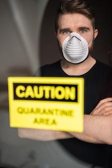 Coronavirus, quarantaine, covid-19 en pandemisch concept. verdrietige en zieke man van het coronavirus kijkt door het raam