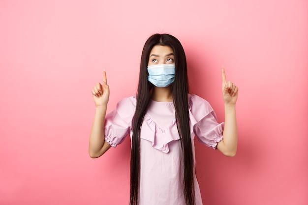 Coronavirus quarantaine en lifestyle concept schattig koreaans meisje met medisch masker dat met de vingers omhoog wijst...