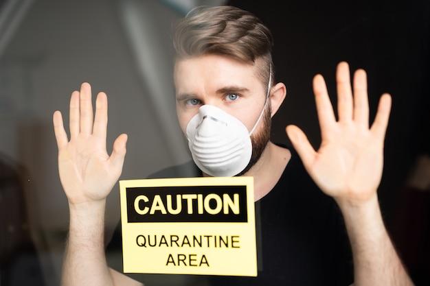 Coronavirus, quarantaine en pandemie concept. verdrietige en zieke man van het coronavirus kijkt door het raam