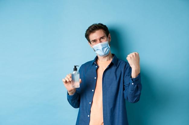 Coronavirus, quarantaine en sociaal afstandsconcept. vrolijke kerel zegt ja en heft vuist op terwijl hij handdesinfecterend middel laat zien, product aanbeveelt, blauwe achtergrond.