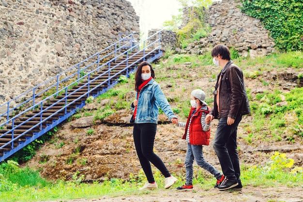 Coronavirus quarantaine. familie-uitstapje naar het oude kasteel. familie wandelen in de buurt van kasteelruïnes.