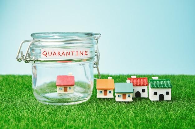 Coronavirus quarantaineconcept. klein huis in een glazen pot en inscriptie quarantaine