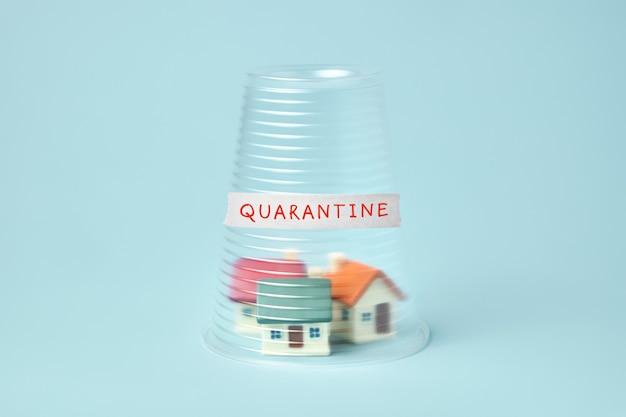 Coronavirus quarantaineconcept. kleine huizen bedekt met doorzichtige plastic beker en inscriptie quarantaine