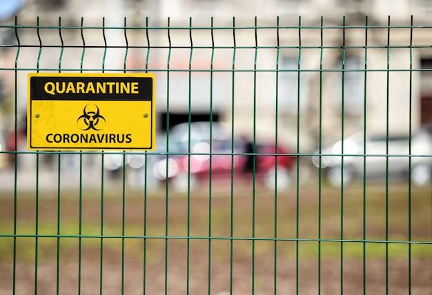 Coronavirus quarantaineteken op groene decoratieve metalen draadomheining