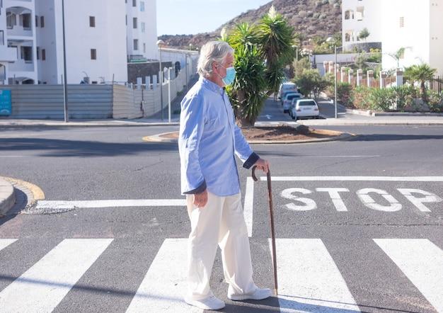 Coronavirus. senior man met een stok loopt op straat met een medisch masker