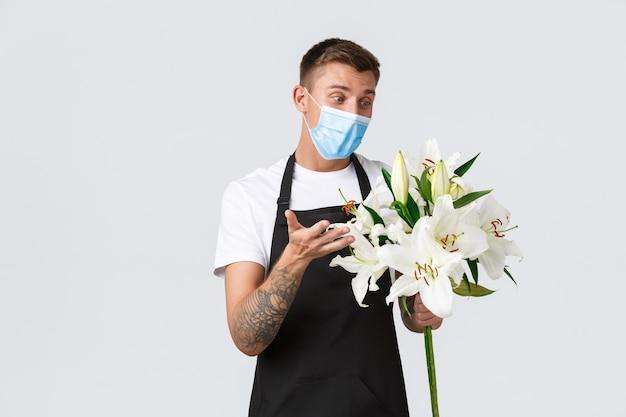 Coronavirus, social distancing business covid-19 pandemisch concept. vriendelijke charismatische bloemist beschrijft hartstochtelijk boeket, verkoopt bloemen, houdt witte lelies vast, draagt een medisch masker