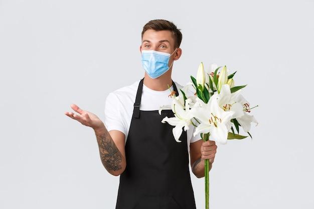 Coronavirus, social distancing business in covid-19 pandemisch concept. vriendelijke charismatische verkoper in schort en medisch masker bereidde een prachtig boeket lelies, pratend met de klant in de bloemenwinkel
