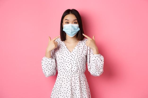 Coronavirus social distancing en lifestyle concept schattige aziatische vrouw wijzend op gezichtsmasker met de vraag om...