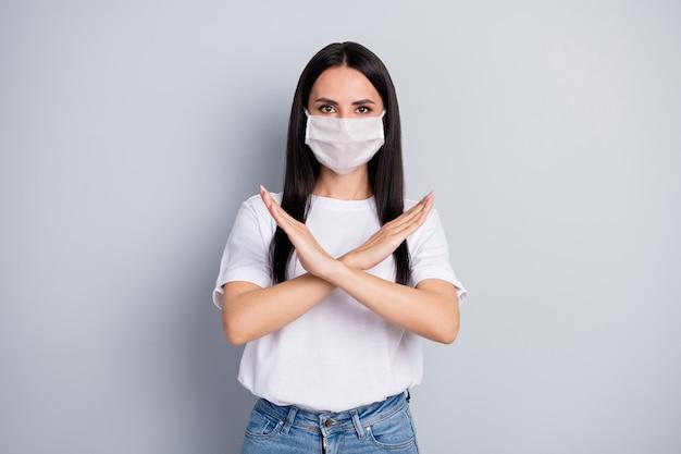 Coronavirus stopt besmetting. zelfverzekerd streng meisje kruis haar handen verbieden gaan lopen lucht dragen witte medische masker tshirt denim jeans geïsoleerd over grijze kleur achtergrond