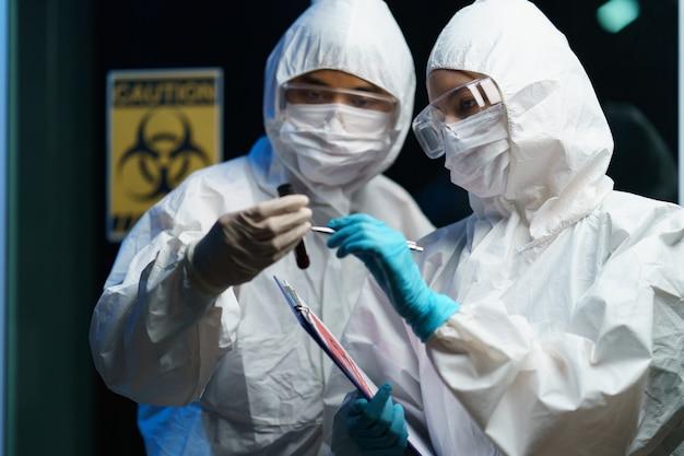Coronavirus testproces: koppel wetenschapper die een medisch masker draagt met een veiligheidsbril in een hazmatpak, met een bloedtestmonster in de hand rapport met informatie over bloedonderzoek.