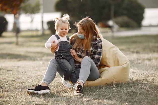 Coronavirus-thema. familie in een zomerpark. vrouw in een celoverhemd.