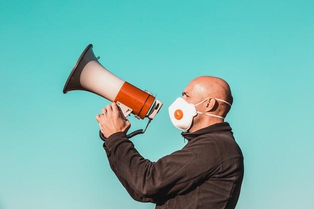 Coronavirus-uitbraak, boze man met medisch gezichtsmasker schreeuwend in de megafoon, coronavirus, covid-2019-protest, economische crisis, wereldwijde pandemie