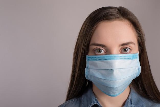 Coronavirus-uitbraak concept. sluit omhoog foto van vrouw die gezichts medisch masker draagt dat tegen pandemie beschermt die over grijze muur met exemplaar lege ruimte wordt geïsoleerd