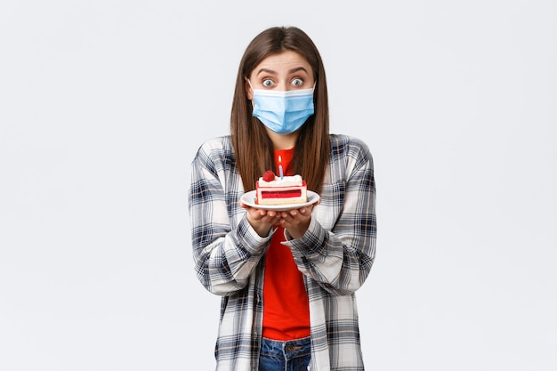 Coronavirus-uitbraak, levensstijl tijdens sociale afstand en vakantievieringsconcept. leuk gelukkig feestvarken dat een wens doet, een medisch masker draagt, een verjaardagstaart vasthoudt, thuis viert.