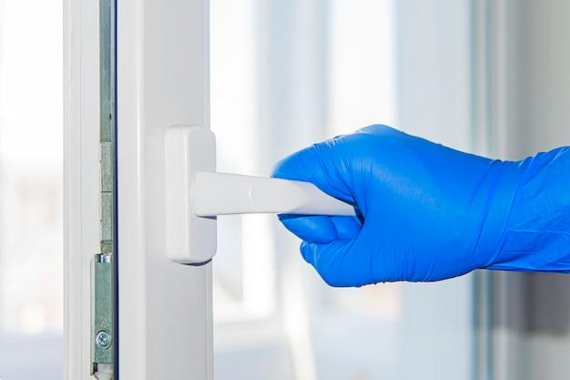 Coronavirus-uitbraak, virus- en herstelconcept, een plastic deur openen. een hand die een deurknop aanraakt met een handschoen om infectie te voorkomen. openbare deurklink is besmet met een coronavirus