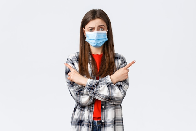 Coronavirus-uitbraak, vrije tijd op quarantaine, sociale afstand en emotiesconcept. besluiteloos en geen idee, mooi meisje met medisch masker, vraag je mening, advies als zijwaarts naar links en rechts wijzend.