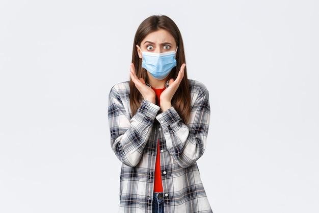 Coronavirus-uitbraak, vrije tijd op quarantaine, sociale afstand en emotiesconcept. bezorgde en geschokte jonge vrouw hoort slecht nieuws. meisje met medisch masker naar adem snakkend en een bezorgde camera kijkend.