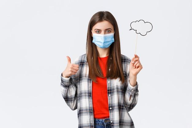 Coronavirus-uitbraak, vrije tijd op quarantaine, sociale afstand en emotiesconcept. blij jong vastberaden meisje met medisch masker duim omhoog, houd bubble commend cloud op stick.