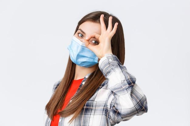 Coronavirus-uitbraak, vrije tijd op quarantaine, sociale afstand en emotiesconcept. dromerig schattig meisje met medisch masker, alles in orde, alles goed, maak een ok-teken boven het oog.