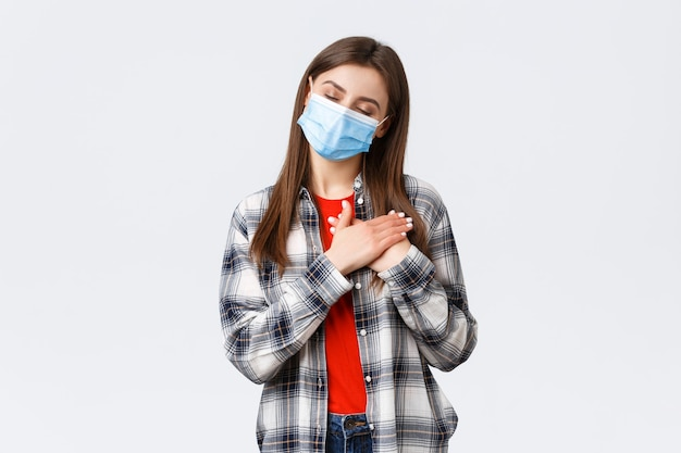 Coronavirus-uitbraak, vrije tijd op quarantaine, sociale afstand en emotiesconcept. dromerige aantrekkelijke jonge vrouw met medisch masker, sluit de ogen beeldvorming of onthoud het geheugen, druk de handen op het hart