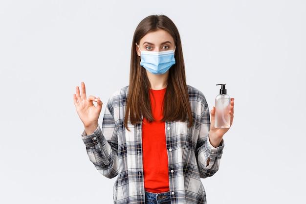Coronavirus-uitbraak, vrije tijd op quarantaine, sociale afstand en emotiesconcept. een tevreden, verzekerde jonge vrouw met een medisch masker raadt aan om dit merk van handdesinfecterend middel te kopen, een goed teken te tonen.